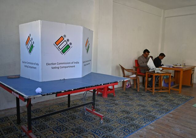 Election officials sit inside an empty polling station during the fifth phase of India's general elections in Kashmir's Shopian district, south of Srinagar, on May 6, 2019