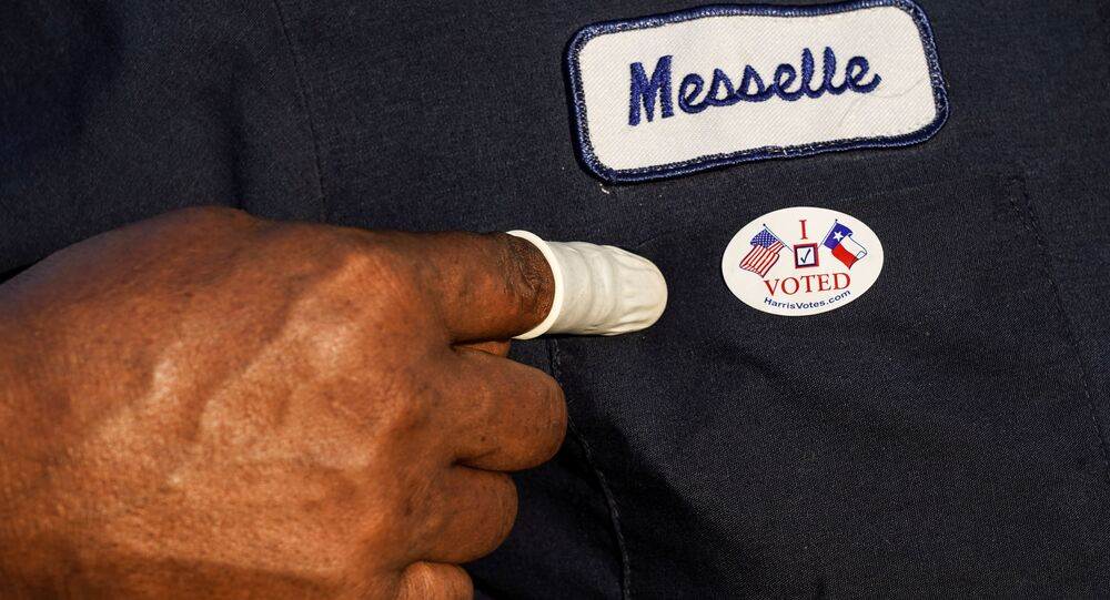A person wearing a finger sack points at an I Voted sticker after casting ballot for the upcoming presidential election as early voting begins in Houston, Texas, U.S., October 13, 2020.