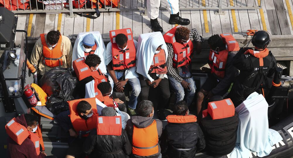 A group of people, thought to be migrants wait on a Border Force rib to come ashore at Dover marina in Kent, England after a small boat incident in the English Channel, Tuesday Sept. 22, 2020.