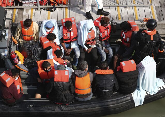 A group of people, thought to be migrants wait on a Border Force RIB to come ashore at Dover marina in Kent, England after a small boat incident in the English Channel, Tuesday 22 September 2020.