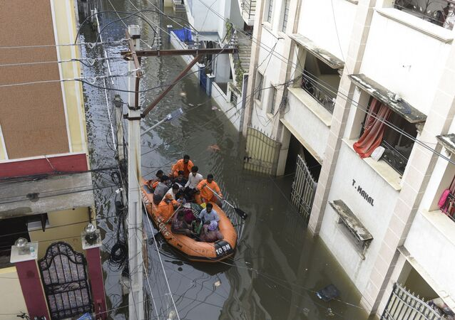 National Disaster Response Force (NDRF) personnel evacuate local residents in a boat along a flooded street following heavy rains in Hyderabad on October 15, 2020.
