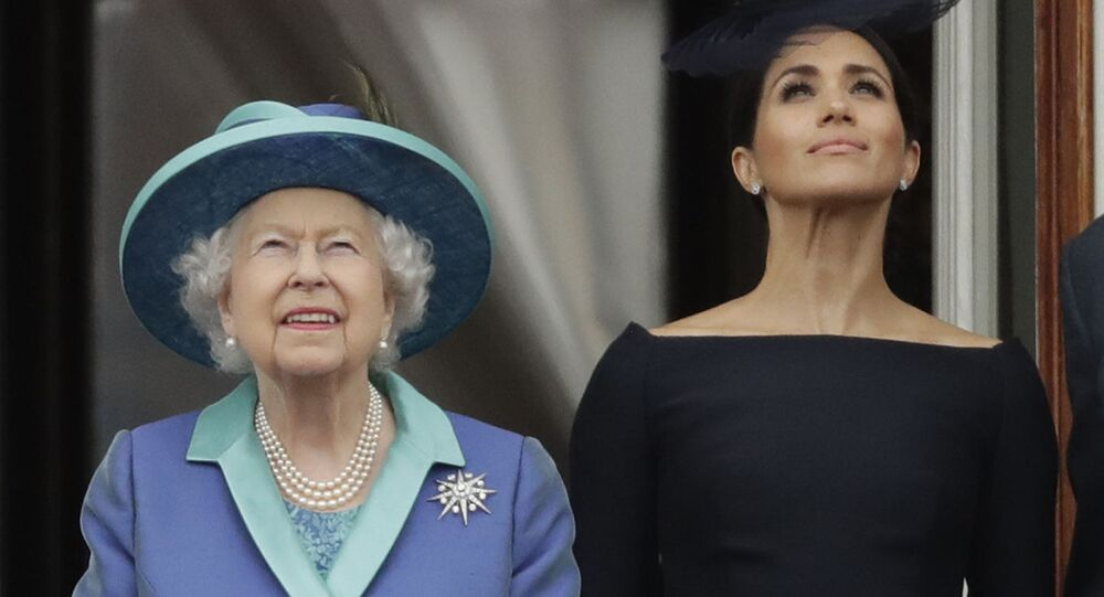 FILE - In this Tuesday, July 10, 2018 file photo Britain's Queen Elizabeth II and Meghan the Duchess of Sussex stand on a balcony to watch a flypast of Royal Air Force aircraft pass over Buckingham Palace in London