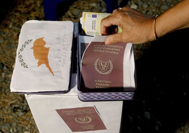 A demonstrator takes a  mock copy of Cyprus passport during a demonstration against corruption outside of the conference center in the capital Nicosia, Cyprus, Wednesday, Oct. 14, 2020.