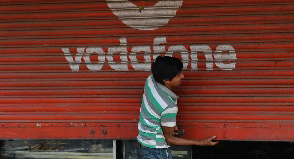 A staff opens the shutter of a shop depicting an advertisement of the telecom company Vodafone in Mumbai on February 21, 2020