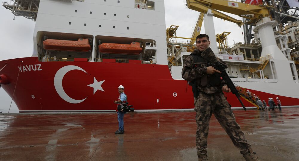 Turkish police officer patrols the dock backdropped by the drilling ship'Yavuz scheduled to be dispatched to the Mediterranean at the port of Dilovasi outside Istanbul