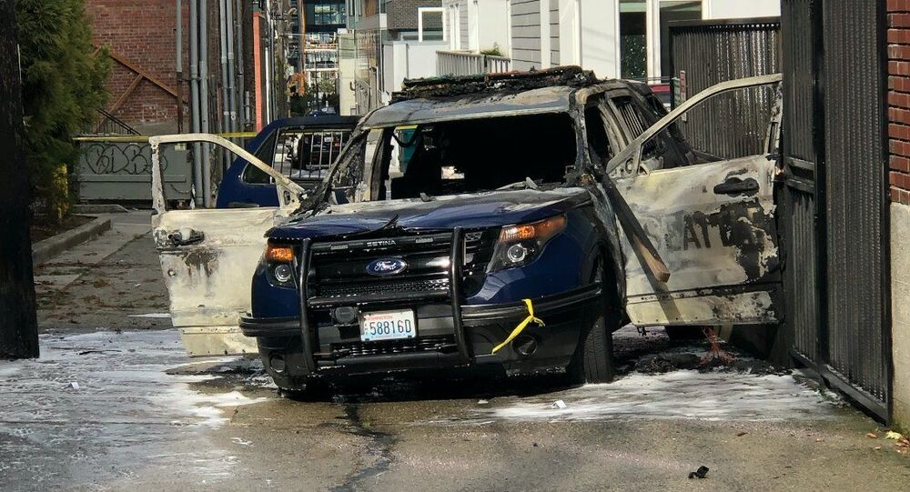 Police arrested a man in S. Lake Union today after he threw burning lumber into a patrol car