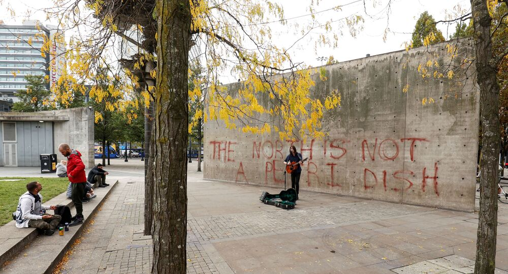 A man plays the guitar in front of Manchester Piccadilly gardens wall with graffiti amid the outbreak of the coronavirus disease (COVID-19), in Manchester, Britain October 16, 2020.