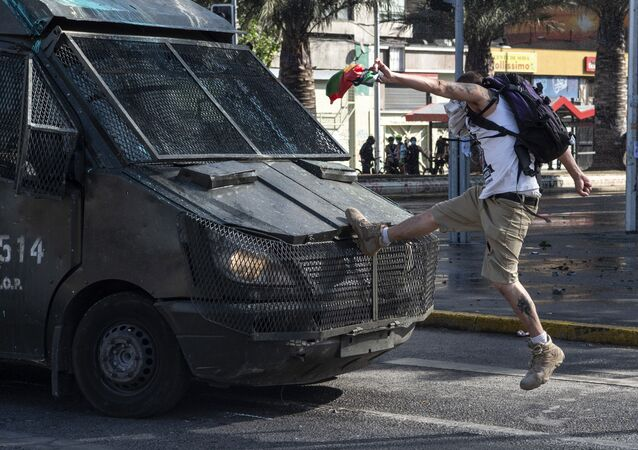 A demonstrator clashes with a riot police van during a protest against Chilean President Sebastian Pinera's government in Santiago on 16 October 2020.