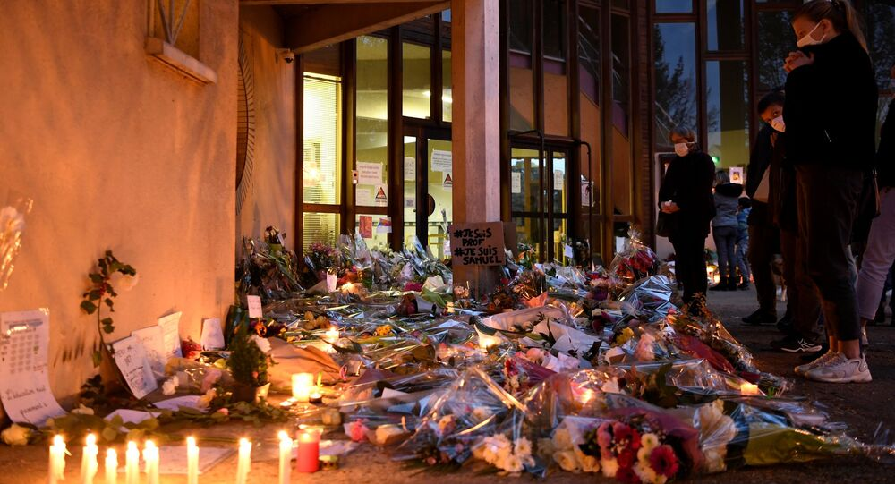 People hold a vigil and lay flowers and candles next to a placard reading 'I am a teacher, I am Samuel' at the entrance of a middle school in Conflans-Sainte-Honorine, 30kms northwest of Paris, on 17 October 2020. History teacher Samuel Paty was beheaded by an attacker after showing his pupils cartoons of the prophet Mohammed. The man suspected of the murder on 16 October 2020 was an 18-year-old who had been born in Moscow and originated from Russia's southern region of Chechnya, a judicial source said on 17 October. Five more people have been detained over the murder including the parents of a child at the school where the teacher was working, bringing to nine the total number currently under arrest, said the source, who asked not to be named. The attack happened at around 5 pm (1500 GMT).