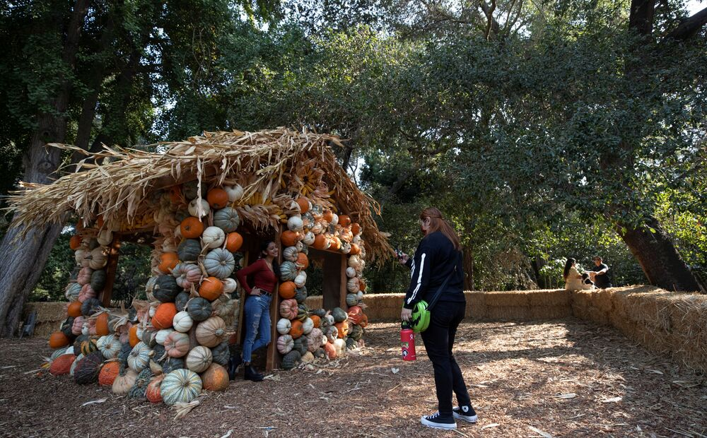 A girl poses inside a pumpkin house installation during the Halloween at Descanso event at Descanso Gardens in La Canada Flintridge, California, US 9 October 2020.
