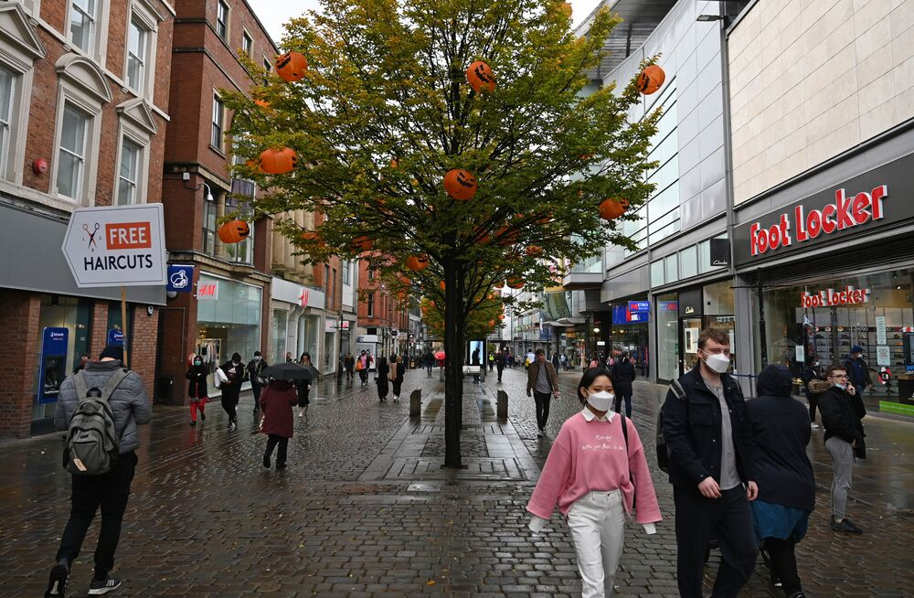 Pedestrians wearing a face mask or covering due to the COVID-19 pandemic, walks past a tree decorated in pumpkins ahead of Halloween, in Manchester, northern England on 6 October 2020, after localised restrictions were introduced across the country's northwest following a spike in coronavirus cases.