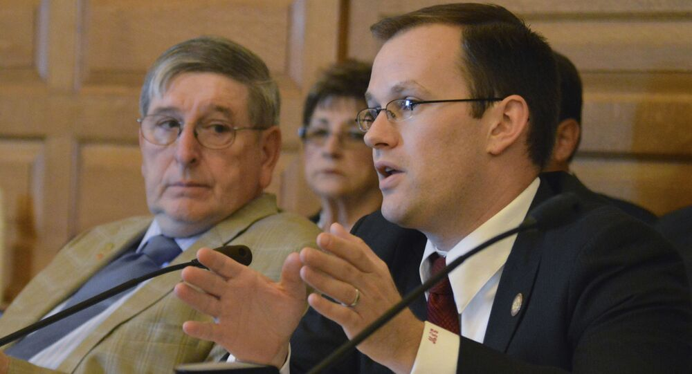 In this May 13, 2015 file photo, Kansas state Rep. Brandon Whipple, D-Wichita, speaks at the Statehouse in Topeka, Kan. Whipple, now the Mayor of Wichita and three City Council members have quarantined themselves after being told  Tuesday, March 17, 2020,  that two people at a conference they attended last week have the coronavirus. Whipple and council members Becky Tuttle, James Clendenin and Brandon Johnson attended the National League of Cities conference in Washington D.C.