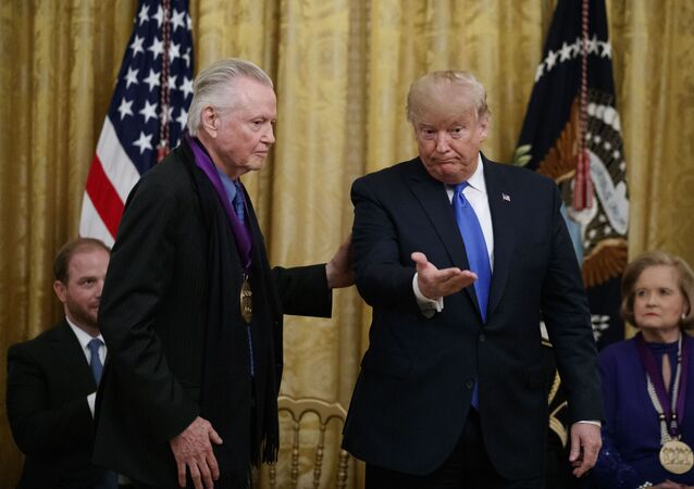 President Donald Trump gestures after presenting a National Medal of the Arts to actor Jon Voight, during a National Medal of Arts and National Humanities Medal ceremony in the East Room of the White House, 21 November 2019