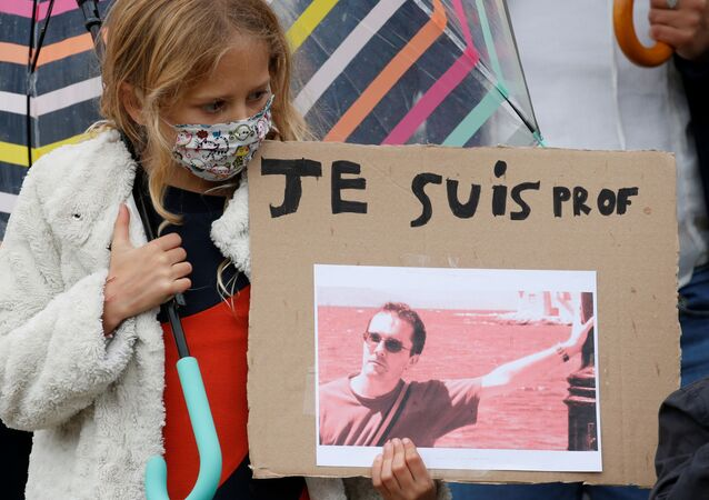 A girl holds a banner with a picture of Samuel Paty, the French teacher who was beheaded on the streets of the Paris suburb of Conflans St Honorine, during a tribute at the Place de la Republique, in Lille, France, 18 October 2020. REUTERS/Pascal Rossignol NO RESALES. NO ARCHIVES.