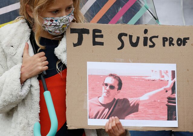 A girl holds a banner with a picture of Samuel Paty, the French teacher who was beheaded on the streets of the Paris suburb of Conflans St Honorine, during a tribute at the Place de la Republique, in Lille, France, October 18, 2020. REUTERS/Pascal Rossignol       NO RESALES. NO ARCHIVES.