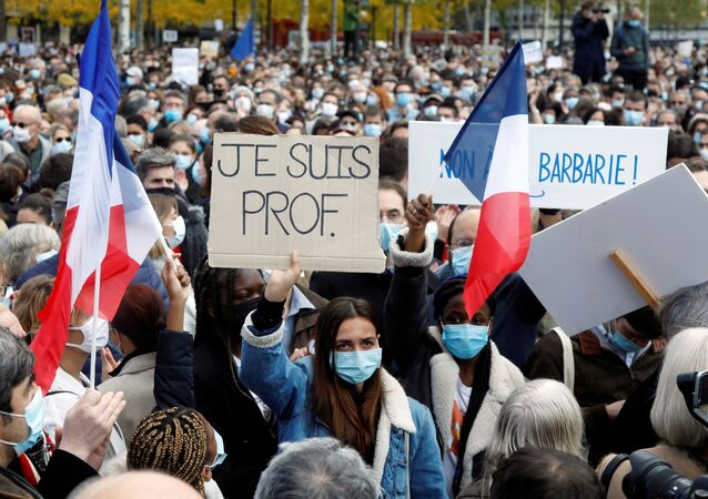 People gather at the Place de la Republique in Paris, to pay tribute to Samuel Paty, the French teacher who was beheaded on the streets of the Paris suburb of Conflans-Sainte-Honorine, France, October 18, 2020.  Placard reads I am a teacher. REUTERS/Charles Platiau