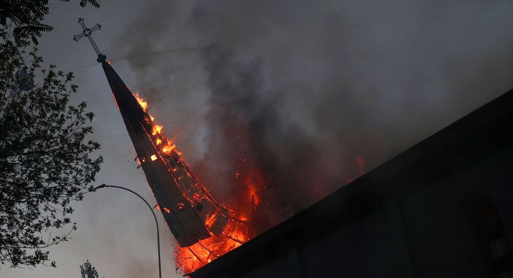 The spire of a church set on fire topples during a protest against Chile's government, on the one-year anniversary of the protests and riots that rocked the capital in 2019, in Santiago, Chile, October 18, 2020.