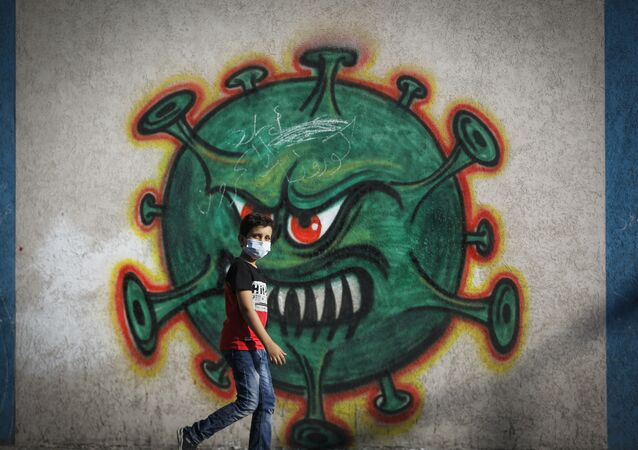 A Palestinian boy walks past street art showing a malevolent coronavirus, in Gaza city on 22 September 2020.