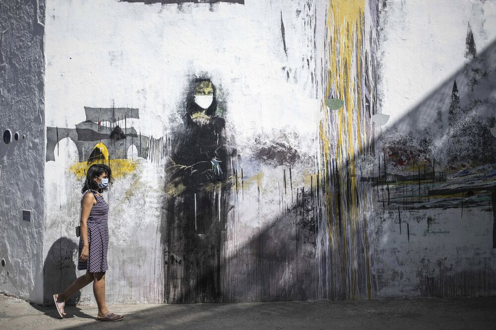 A woman wearing a face mask to prevent the spread of coronavirus walks past a mural of a mask-wearing Mona Lisa, in the Medina of Asilah, northern Morocco, 19 September 2020. The town is known for its well-preserved ramparts, which were built by the Portuguese in the 15th century, and is nowadays a hub for street art and cultural events.