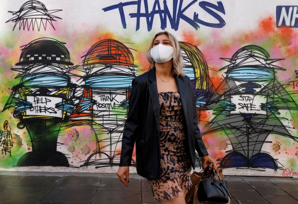 A woman wearing a face mask stands in front of graffiti, amid the coronavirus disease (COVID-19) outbreak, in central London, Britain on 15 October 2020.