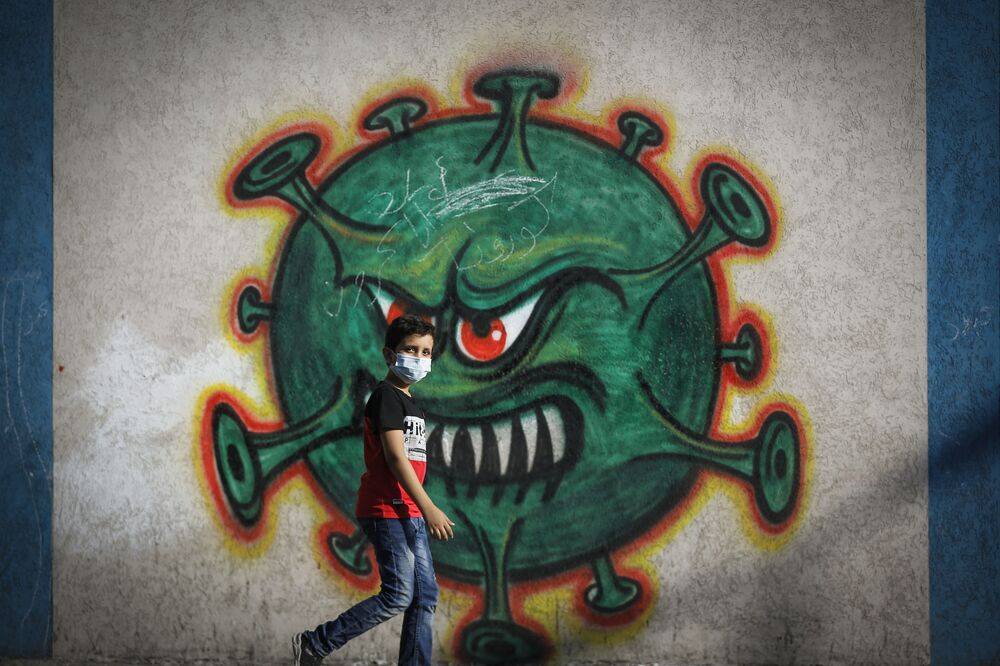 A Palestinian boy walks past street art showing a malevolent coronavirus, in Gaza city on 22 September 2020.