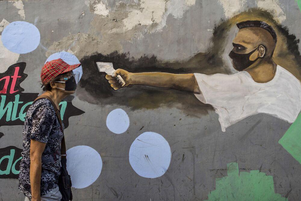 An elderly woman walks past a mural depicting the COVID-19 coronavirus in Surabaya, East Java on 30 September 2020.