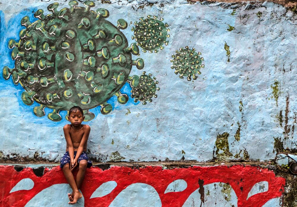 A young boy sits in front of a mural representing the Covid-19 coronavirus in Bogor, West Java on 27 September 2020.