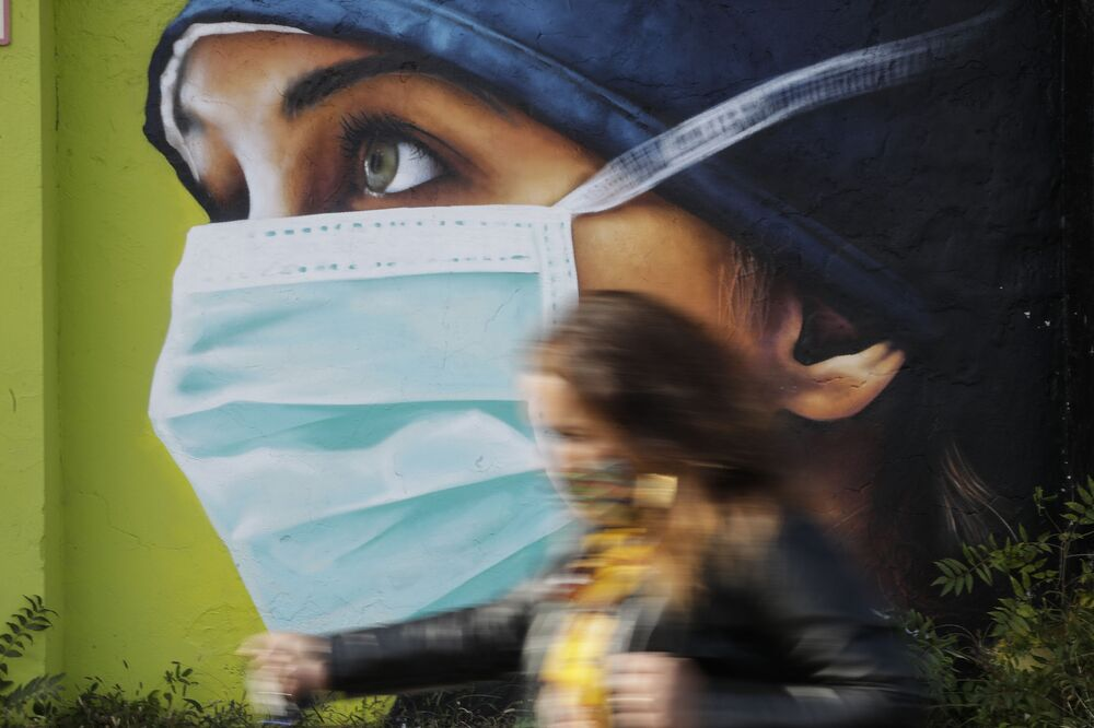 A woman walks in from of a mural painting of a nurse, in Milan, Italy, 14 October 2020. Coronavirus infections are surging again in the Italian northern region where the pandemic first took hold in Europe, putting pressure again on hospitals and health care workers.