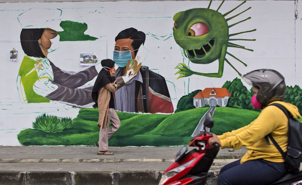 People pass a coronavirus-themed mural intended to remind people to always wear mask in public places, in Medan, North Sumatra, Indonesia, 18 September 2020.