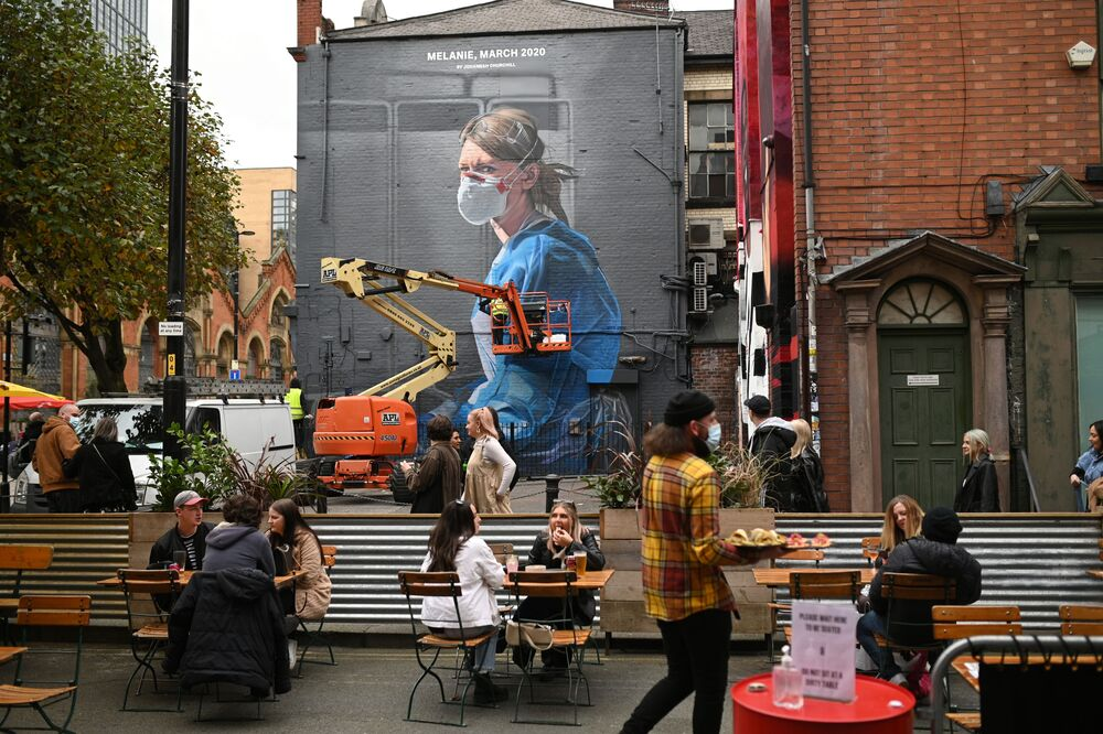 People enjoy a socially-distanced drink as an artist creates a mural of a NHS worker on a wall in north Manchester on 17 October 2020, as the number of cases of the novel coronavirus COVID-19 rises.