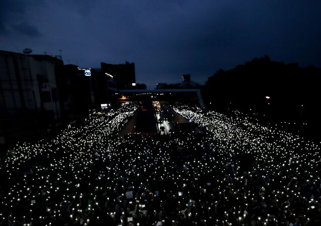 Pro-democracy activists wave mobile phones with lights during a demonstration at Kaset intersection, suburbs of Bangkok, Thailand, Monday, Oct. 19, 2020. Thai authorities worked Monday to stem a growing tide of protests calling for the prime minister to resign by threatening to censor news coverage, raiding a publishing house and attempting to block the Telegram messaging app used by demonstrators.