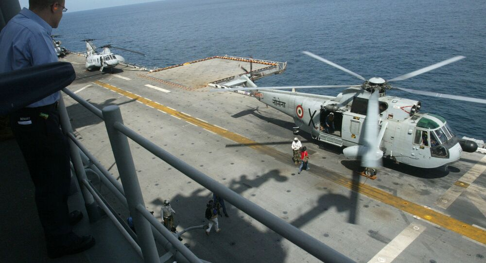 A U.S. Navy officer, left, looks on as an Indian Navy Sea King helicopter prepares to take-off from the USS Boxer, an amphibious assault ship, during the India-US joint naval exercise, 'Malabar-06', in the Arabian Sea, India, Sunday, Oct. 29, 2006. Eleven ships and two submarines from the two nations are participating in these joint exercises which began on Oct. 25 and will end on Nov. 5,  focusing on a variety of functional skill areas, including force protection drills, formation steaming, amphibious landing and anti-submarine warfare training.