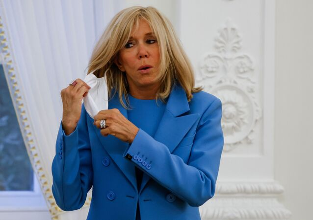 In this file photo taken on September 28, 2020, French President's wife Brigitte Macron takes off her face mask after a welcoming ceremony at the Presidential Palace in Vilnius, Lithuania. - Brigitte Macron has gone into a 7-day self-isolation period after being in contact with a person who has been tested positive with Covid-19, her entourage told AFP on October 19, 2020. Brigitte Macron, who does not show any symptoms of the disease, was in contact on October 15 with a person declared positive for Covid-19 on October 19, and showing symptoms, according to her entourage.