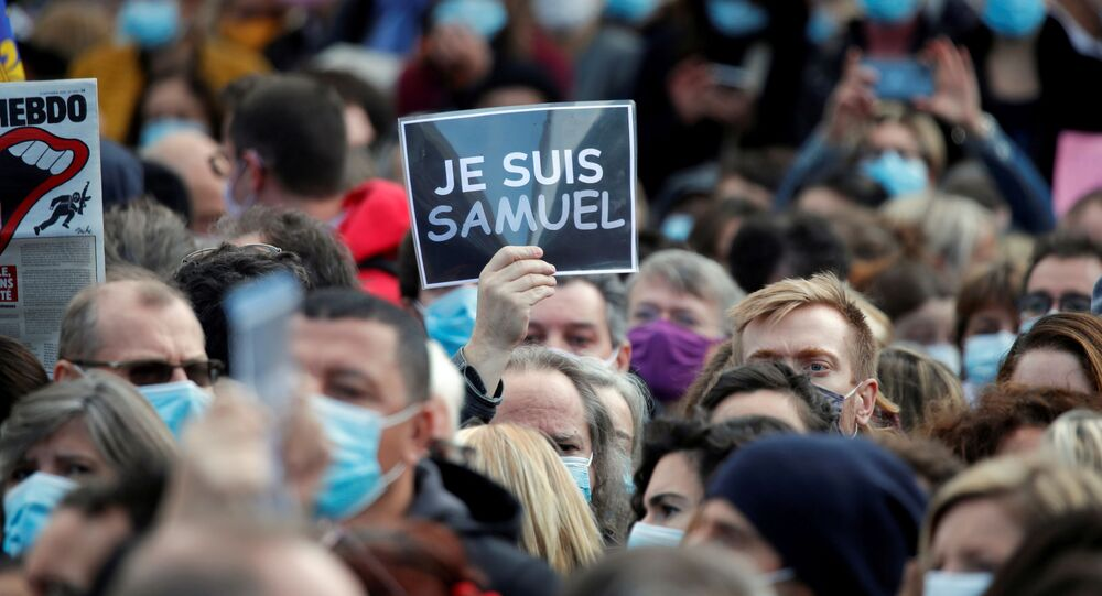 People gather at the Place de la Republique in Paris, to pay tribute to Samuel Paty, the French teacher who was beheaded on the streets of the Paris suburb of Conflans-Sainte-Honorine, France, 18 October 2020.