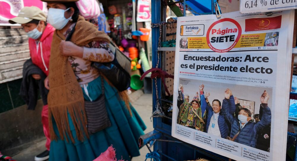 Women walk past a newspaper stand and a headline reading Pollsters: Arce is the president-elect  , in La Paz, Bolivia October 19, 2020.