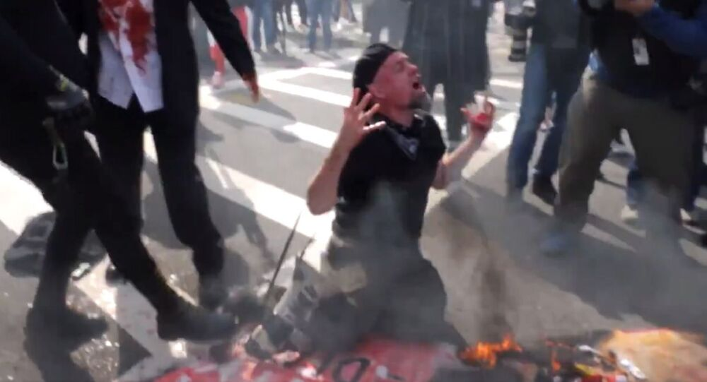 Antifa burn the US flag and eat a heart symbolic of the President during an anti-democrat violence protest in Boston Massachusetts on 10.18.2020