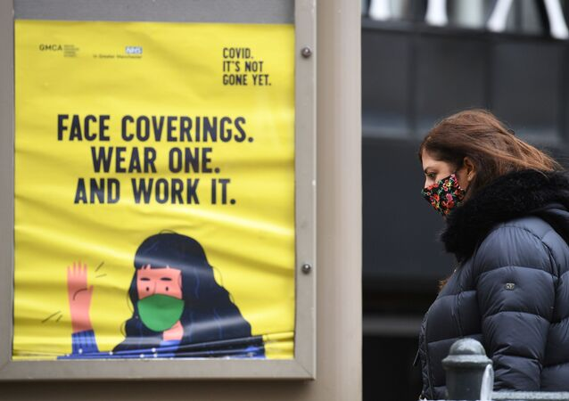 A woman wearing a facemask walks past a poster urging people to wear face coverings, in Manchester, north west England on October 13, 2020, as the number of cases of the novel coronavirus COVID-19 continue to rise.