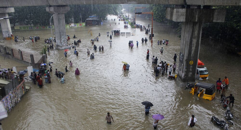 People wade through a flooded road in Chennai, Tamil Nadu, India, Wednesday, Dec. 2, 2015