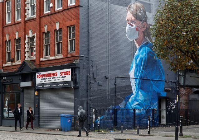 People walk past a mural, as the coronavirus disease (COVID-19) outbreak continues, in Manchester, Britain October 19, 2020