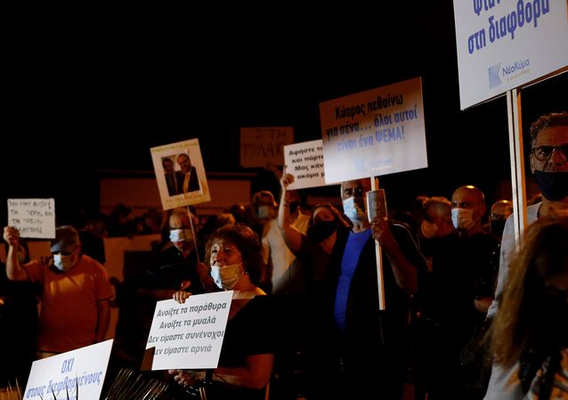 Demonstrators with placards reading in Greek , second right, Cyprus I die for you, they are all a lie and on the left, Open the windows open the minds we are not complicit we are not lambs during a demonstration against corruption outside of the conference center in the capital Nicosia, Cyprus, Wednesday, Oct. 14, 2020.