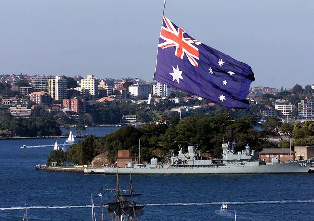 An Australian Navy helicopter hangs a large flag over the HM Bark Endeavour, a full scale replica of Captain James Cook's original 18th century ship, as she sails into Sydney Harbour 03 June 2000