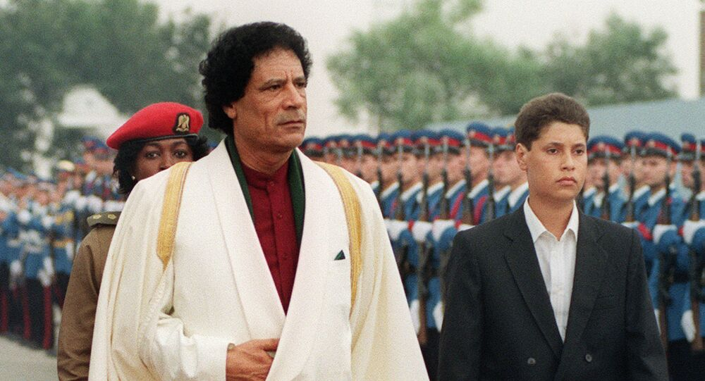 Libyan Head of State Colonel Muammar Gaddafi (L) and his son Saif al-Islam Gaddafi review troops 3 September 1989 upon their arrival in Belgrade before the Non-Aligned Summit.