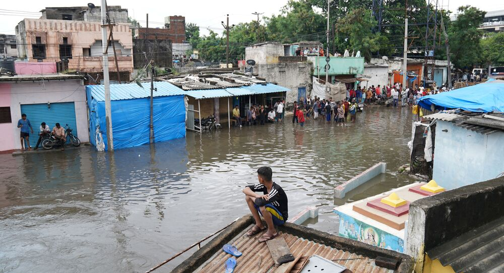 People are seen in a flooded residential area after heavy rainfall in Hyderabad