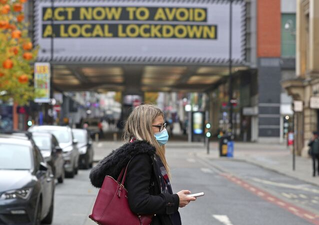 A woman wearing a face mask walks in Manchester, England, Monday, Oct. 19, 2020