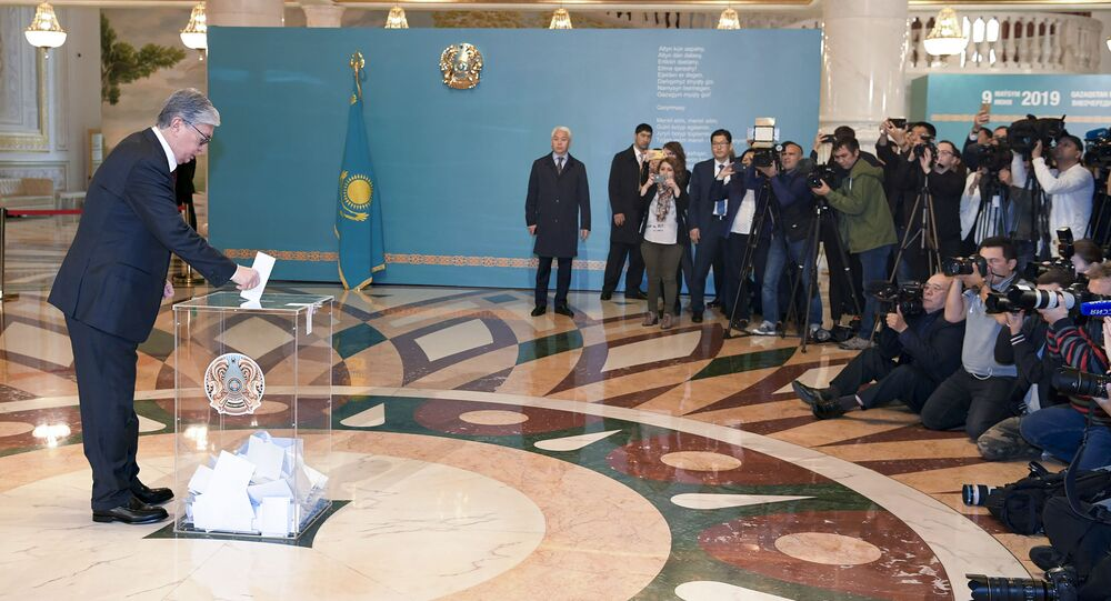 Kazakhstan's acting President Kassym-Jomart Tokayev, left, casts his ballot at a polling station during the presidential elections in Nur-Sultan, the capital city of Kazakhstan, Sunday, June 9, 2019