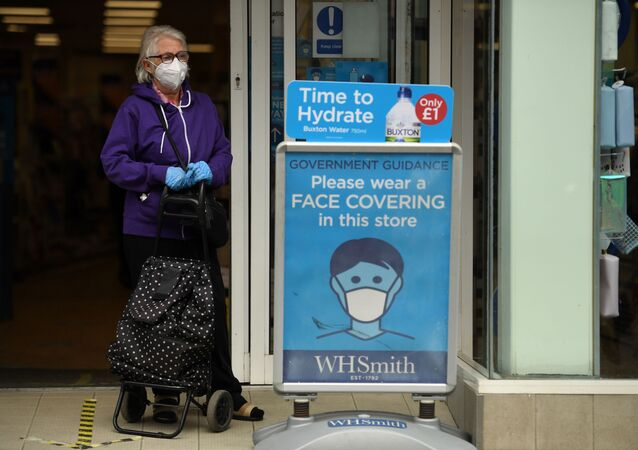 A shopper wearing a face mask stands alongside a sign calling for the wearing of face coverings in shops, in the city centre of Sheffield, south Yorkshire on July 24, 2020, as lockdown restrictions continue to be eased during the novel coronavirus COVID-19 pandemic