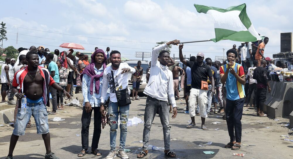 A protester waves a Nigerian national flag behind barricades mounted on the Lagos-Ibadan expressway to protest against police brutality and the killing of protesters by the military, at Magboro, Ogun State, on October 21, 2020
