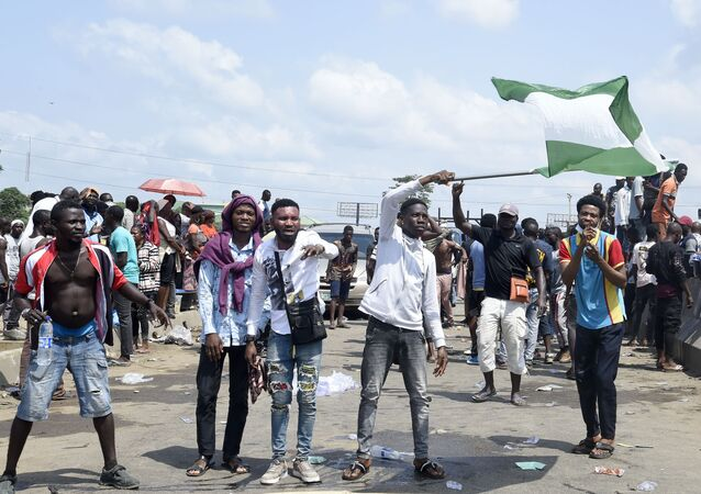 A protester waves a Nigerian national flag behind barricades mounted on the Lagos-Ibadan motorway to protest against police brutality and the killing of protesters by the military, at Magboro, Ogun State, on 21 October 2020.