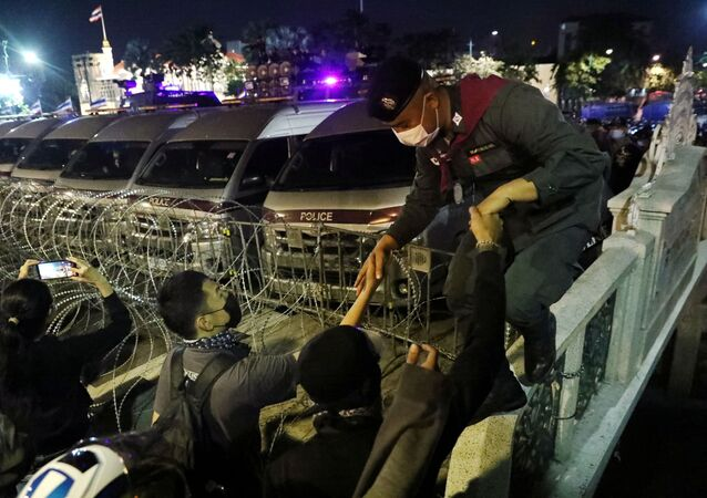 Demonstrators help a police officer outside the Government House during an anti-government protest in Bangkok, Thailand October 21, 2020.