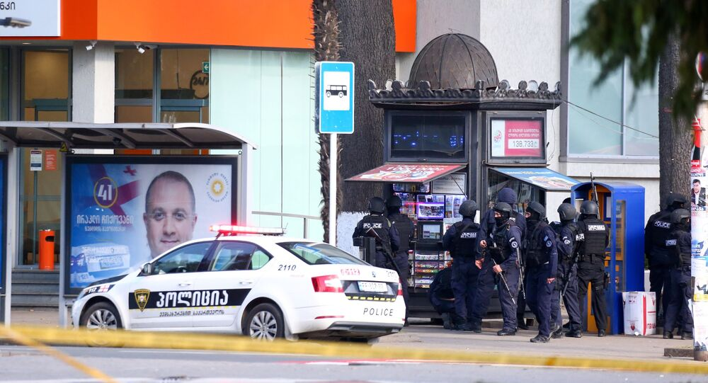Law enforcement officers are seen near a bank branch after an unidentified man reportedly took hostages, in the western Georgian city of Zugdidi on October 21, 2020.